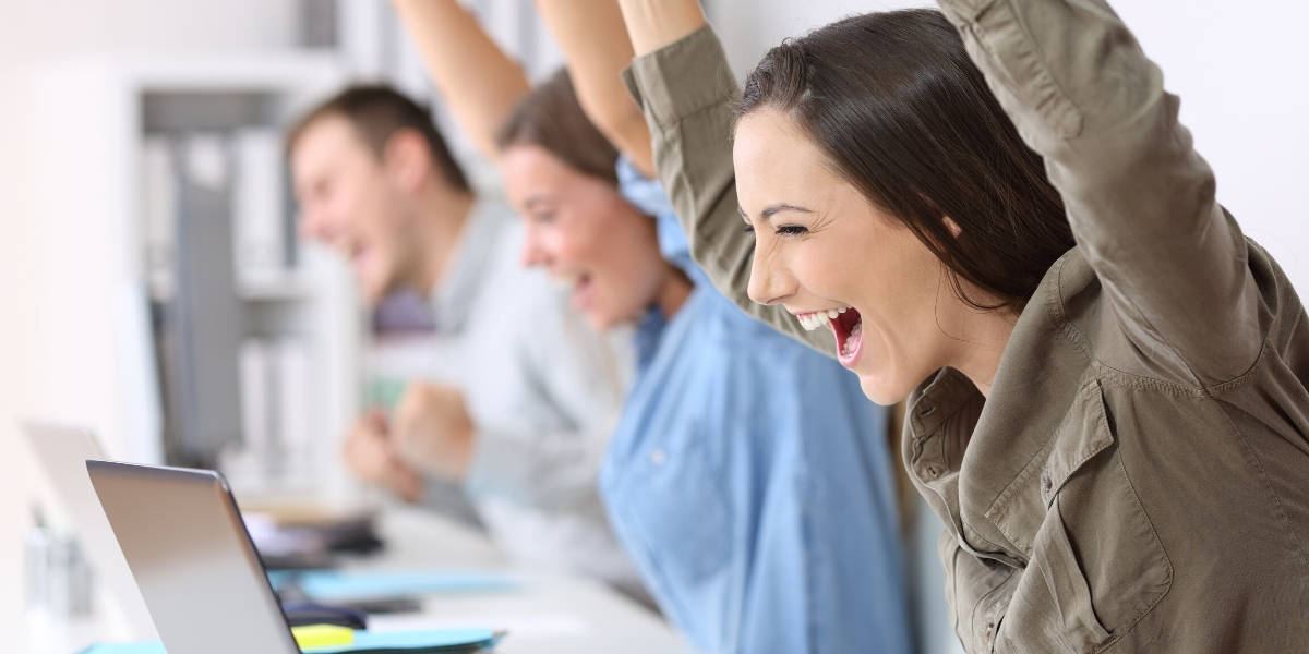Employees in office arms up and happy