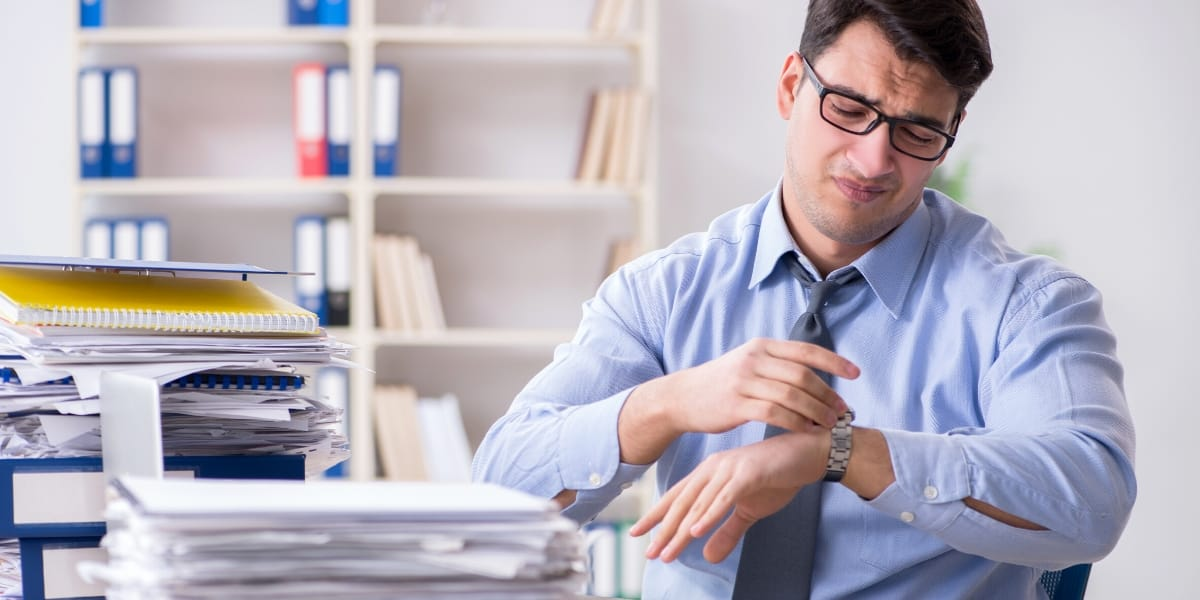 Man at desk looking at watch