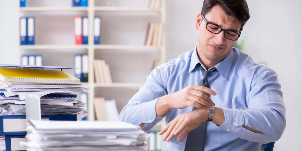 Man at desk looking at watch