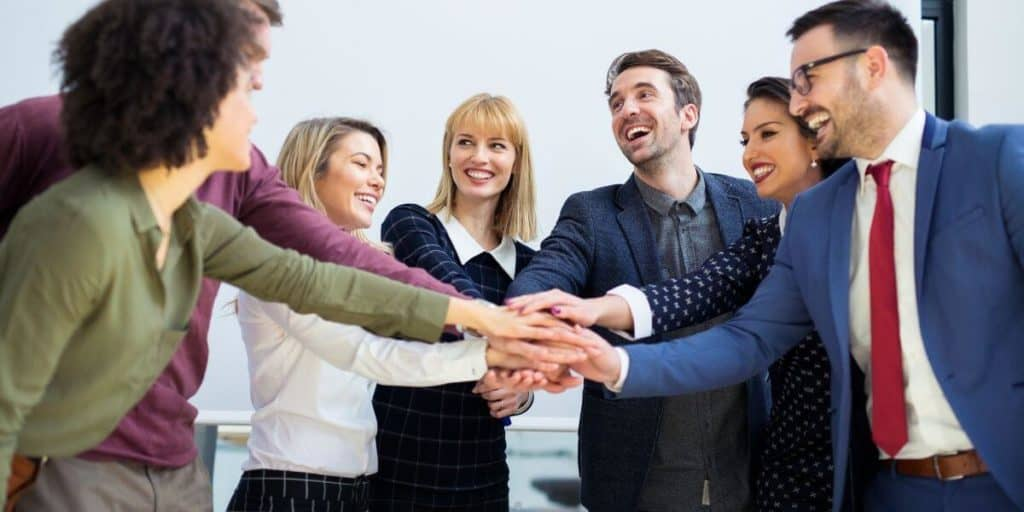people in office hands together