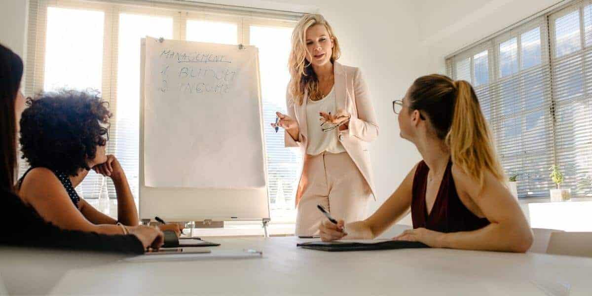 woman standing in leadership in office meeting