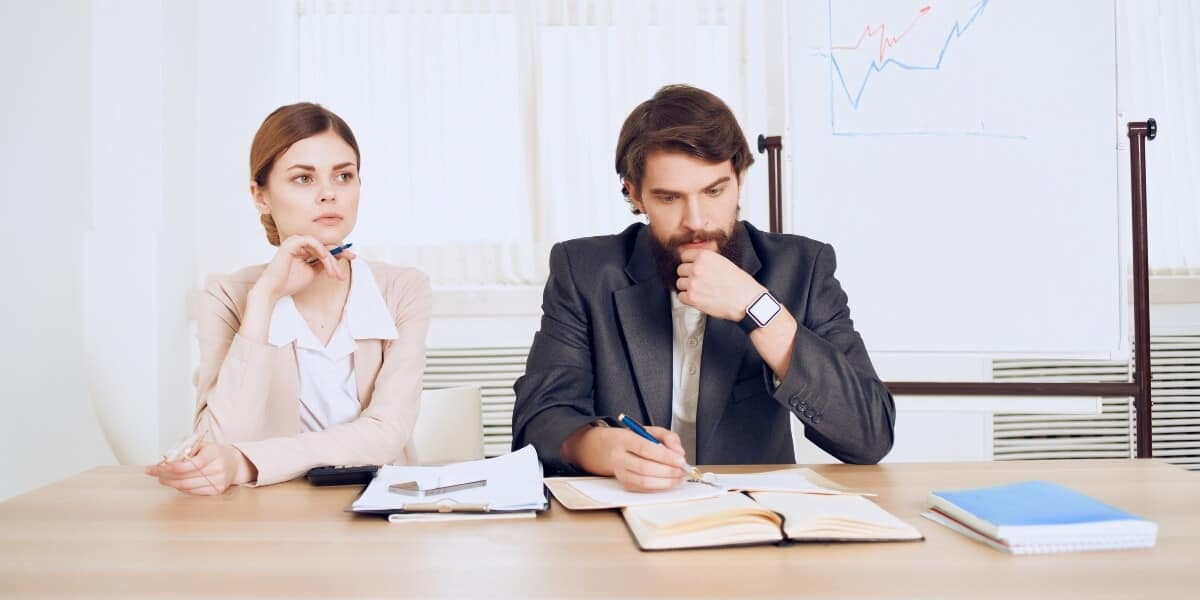 man and woman sitting at desk in conflict