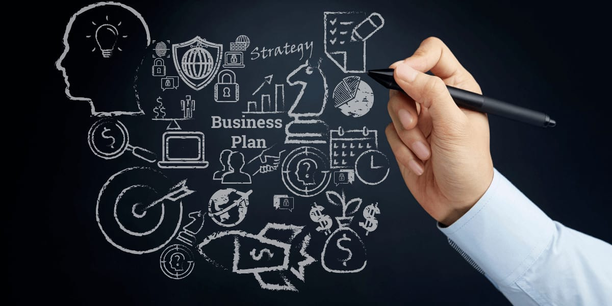 man writing business plan on black board