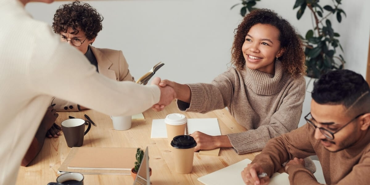 woman happy shaking coworkers hand