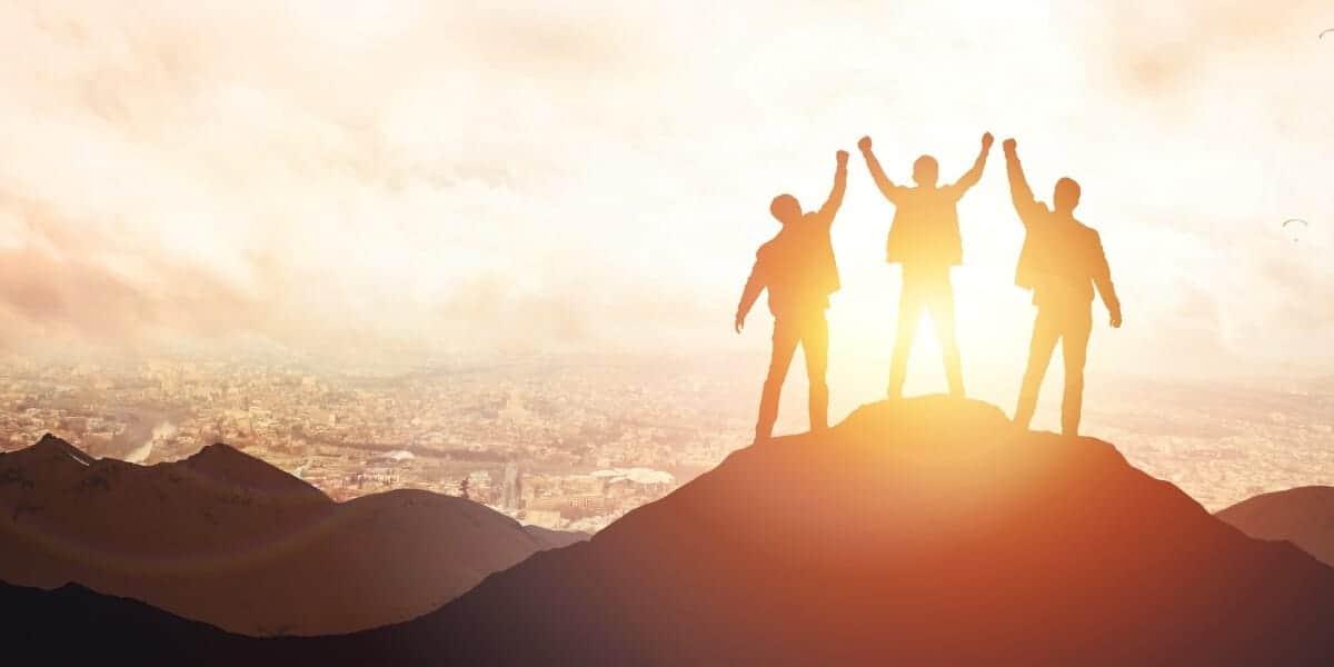 three men raining hands on a mountain