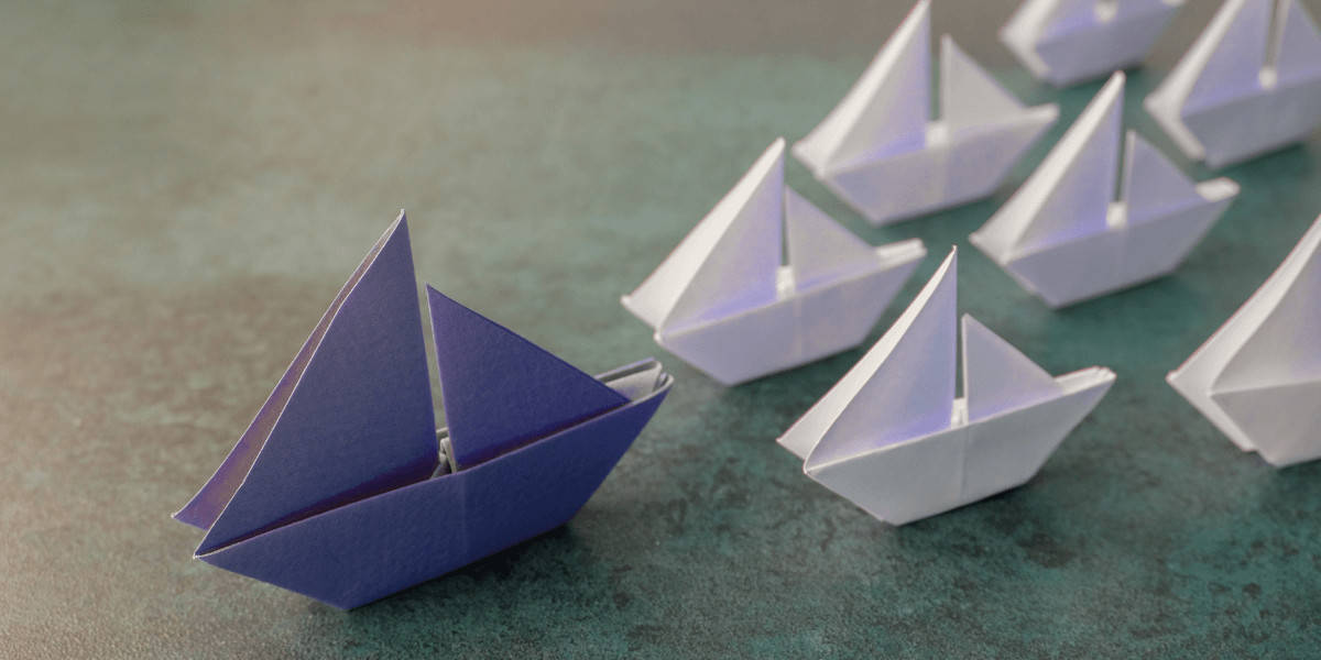 Blue paper boat leading white paper boats
