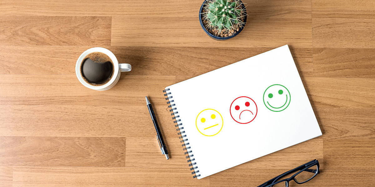 Notebook on desk with drawing of happy, sad and neutral face