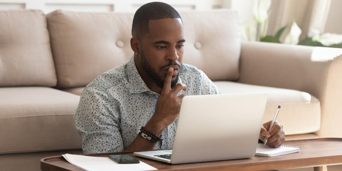 Man sitting at computer researching ICF Certifications